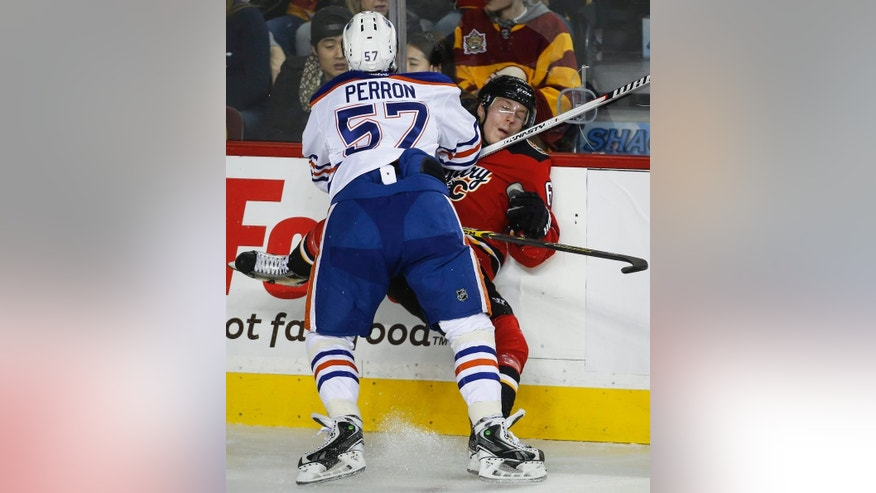 Edmonton Oilers' David Perron, left, checks Calgary Flames' Dennis Wideman during the second period of an NHL hockey game Saturday, Dec. 27, 2014, in Calgary, Alberta. (AP Photo/The Canadian Press, Jeff McIntosh)