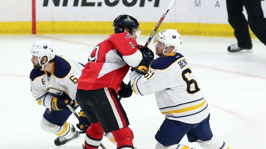 Ottawa Senators' Bobby Ryan (6) is checked by Buffalo Sabres' Andre Benoit, right, and Mike Weber (6) during the second period of an NHL hockey game in Ottawa, Ontario, Monday, Dec. 29, 2014. (AP Photo/The Canadian Press, Fred Chartrand)