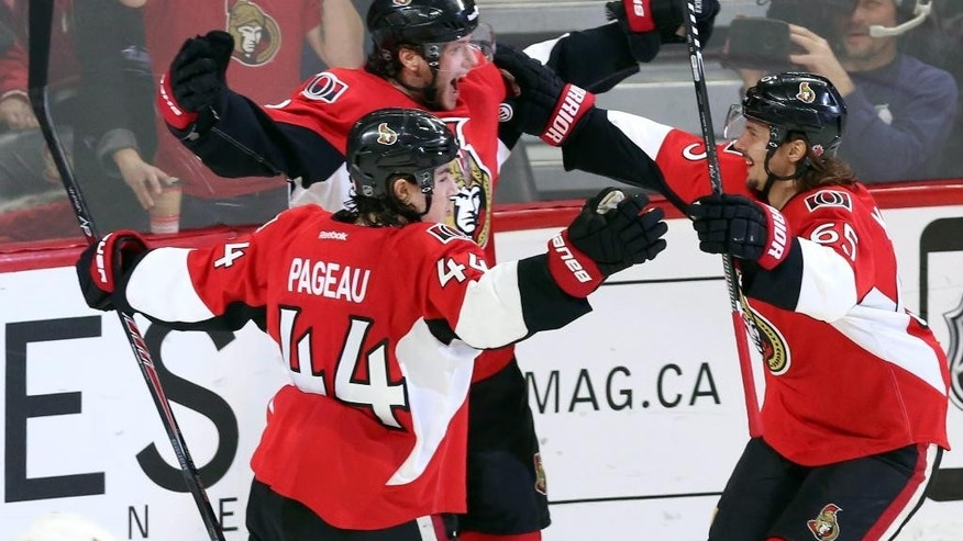 Ottawa Senators' Bobby Ryan (6) celebrates his third goal against the Buffalo Sabres with teammates Erik Karlsson (65) and Jean-Gabriel Pageau (44) during the third period of an NHL hockey game in Ottawa, Ontario, Monday, Dec. 29, 2014. Ottawa won 5-2. (AP Photo/The Canadian Press, Fred Chartrand)