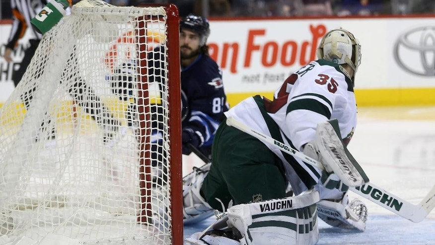 Winnipeg Jets' Mathieu Perreault (85) scores on Minnesota Wild goaltender Darcy Kuemper (35) during the second period of an NHL hockey game in Winnipeg, Manitoba, Monday, Dec. 29, 2014. (AP Photo/The Canadian Press, Trevor Hagan)