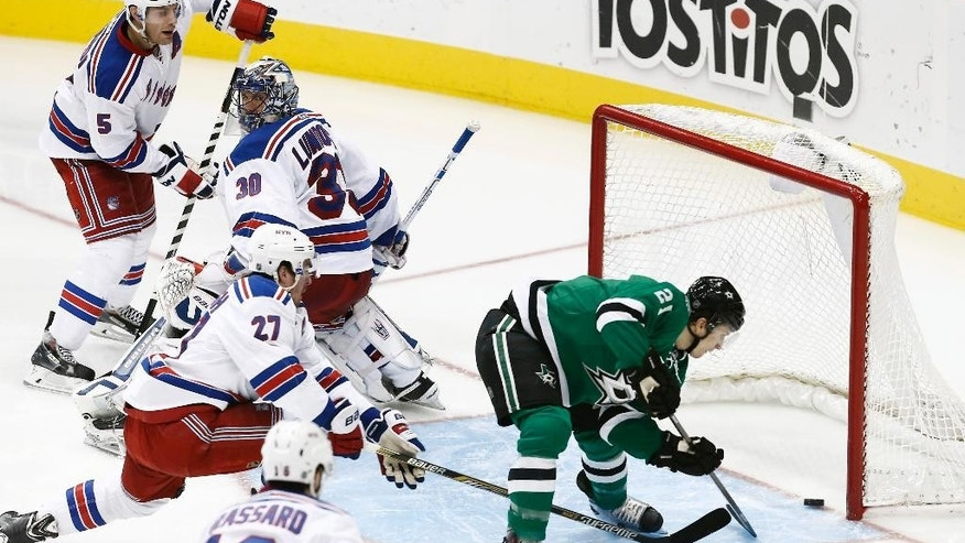 Dallas Stars forward Antoine Roussel (21) shoots a loose puck into the net as New York Rangers defenseman Dan Girardi (5), goalie Henrik Lundqvist (30), defenseman Ryan McDonagh (27) and forward Derick Brassard (16) look on during the second period of an NHL hockey game, Monday, Dec. 29, 2014, in Dallas. (AP Photo/Brandon Wade)