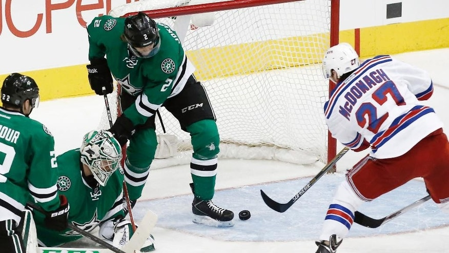 New York Rangers defenseman Ryan McDonagh (27) is unable to reach a rebound as Dallas Stars defenseman Jyrki Jokipakka (2), goalie Kari Lehtonen (32) and forward Colton Sceviour (22) defend during the second period of an NHL hockey game, Monday, Dec. 29, 2014, in Dallas. (AP Photo/Brandon Wade)
