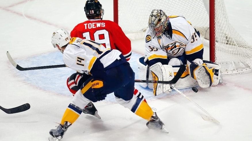 Nashville Predators goalie Pekka Rinne (35) stops a shot by Chicago Blackhawks center Jonathan Toews (19) during the third period of an NHL hockey game Monday, Dec. 29, 2014, in Chicago. The Blackhawks won 5-4 in a shootout. (AP Photo/Jeff Haynes)