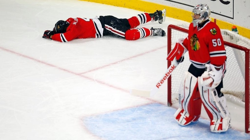 Chicago Blackhawks defenseman Niklas Hjalmarsson (4) lies on the ice after being checked into the boards during the third period of an NHL hockey game against the Nashville Predators, Monday, Dec. 29, 2014, in Chicago. The Blackhawks won 5-4 in a shootout. (AP Photo/Jeff Haynes)