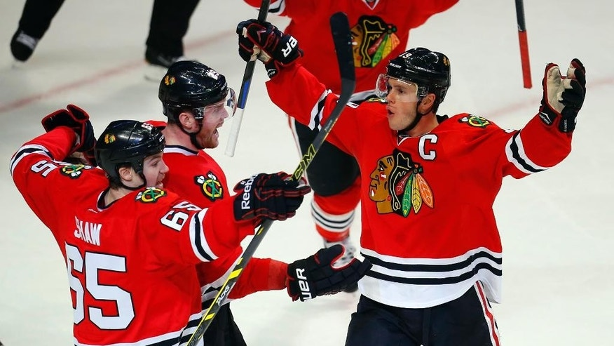 Chicago Blackhawks left wing Bryan Bickell (29) celebrates with teammates center Jonathan Toews (19) and Andrew Shaw (65) after scoring the tying goal in the third period against the Nashville Predators during an NHL hockey game Monday, Dec. 29, 2014, in Chicago. The Blackhawks won 5-4 in a shootout. (AP Photo/Jeff Haynes)