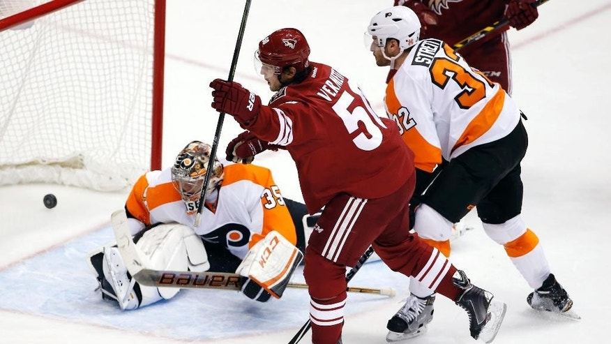 Arizona Coyotes' Antoine Vermette, middle, celebrates his goal against Philadelphia Flyers' Steve Mason (35) as Flyers' Mark Streit (32), of Switzerland, looks on during the second period of an NHL hockey game Monday, Dec. 29, 2014, in Glendale, Ariz. (AP Photo/Ross D. Franklin)
