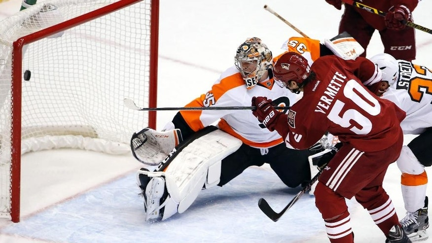 Arizona Coyotes' Antoine Vermette (50) scores a goal against Philadelphia Flyers' Steve Mason (35) during the second period of an NHL hockey game Monday, Dec. 29, 2014, in Glendale, Ariz. (AP Photo/Ross D. Franklin)