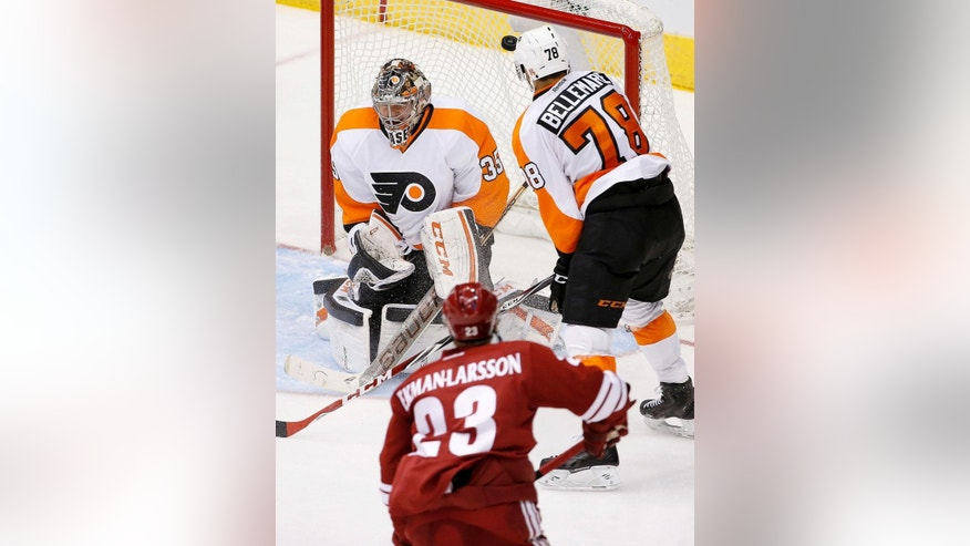 Arizona Coyotes' Oliver Ekman-Larsson (23), of Sweden, threads the defense of Philadelphia Flyers goalie Steve Mason (35) and Pierre-Edouard Bellemare (78) for a goal during the third period of an NHL hockey game Monday, Dec. 29, 2014, in Glendale, Ariz.  The Coyotes won 4-2. (AP Photo/Ross D. Franklin)