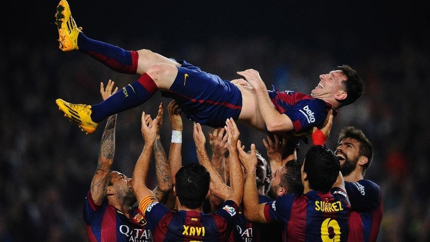 FILE - In this Saturday, Nov. 22, 2014, file photo FC Barcelona's Lionel Messi, from Argentina, is lifted by his teammates after scoring against Sevilla during a Spanish La Liga soccer match between FC Barcelona and Sevilla, at the Camp Nou stadium in Barcelona, Spain.  Messi set a La Liga scoring record of 253 goals when he claimed a hat-trick in Saturday's match at the Camp Nou stadium against Sevilla. (AP Photo/Manu Fernandez, File)