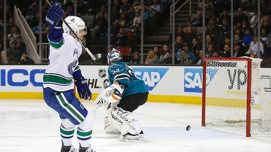 Vancouver Canucks right wing Jannik Hansen (36), of Denmark, celebrates after scoring a goal past San Jose Sharks goalie Alex Stalock (32) during the second period of an NHL hockey game Tuesday, Dec. 30, 2014, in San Jose, Calif. (AP Photo/Tony Avelar)