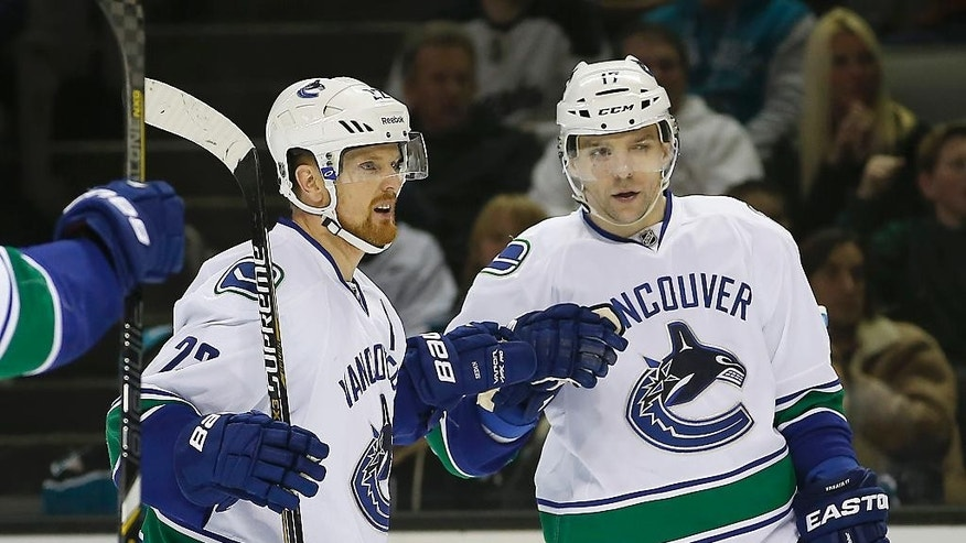 Vancouver Canucks right wing Radim Vrbata (17), from the Czech Republic, celebrates with Vancouver Canucks left wing Daniel Sedin (22), of Sweden, after scoring a goal against San Jose Sharks during the second period of an NHL hockey game Tuesday, Dec. 30, 2014, in San Jose, Calif. (AP Photo/Tony Avelar)