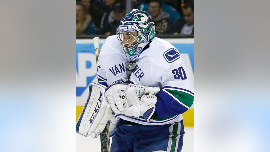 Vancouver Canucks goalie Ryan Miller (30) blocks a goal attempt by the San Jose Sharks during the first period of an NHL hockey game Tuesday, Dec. 30, 2014, in San Jose, Calif. (AP Photo/Tony Avelar)