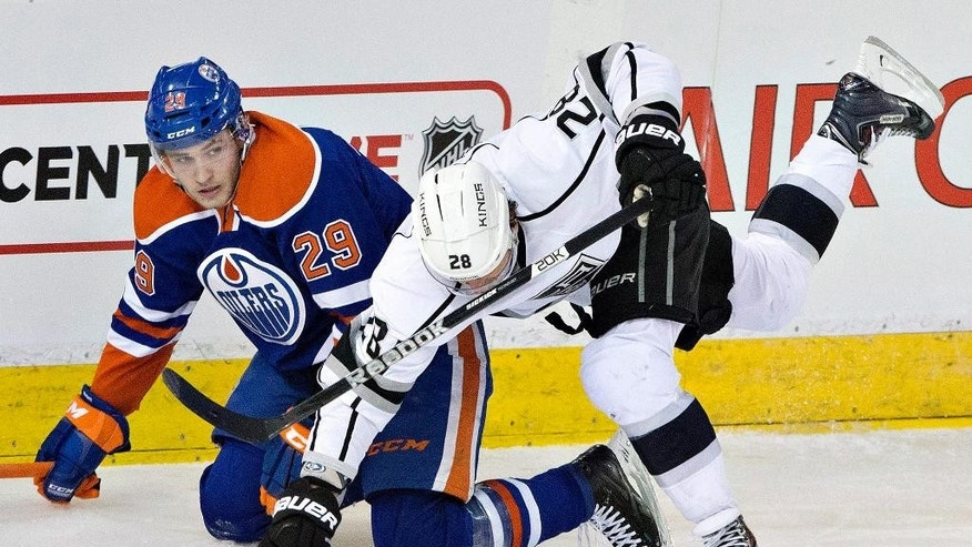 Los Angeles Kings' Jarret Stoll (28) is tripped by Edmonton Oilers' Leon Draisaitl (29) during the second period of an NHL hockey game Tuesday, Dec. 30, 2014, in Edmonton, Alberta. (AP Photo/The Canadian Press, Jason Franson)