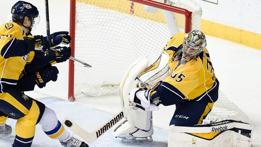 Nashville Predators goalie Pekka Rinne (35), of Finland, clears the puck as bodies slide into his crease against the St. Louis Blues in the second period of an NHL hockey game Tuesday, Dec. 30, 2014, in Nashville, Tenn. (AP Photo/Sanford Myers)