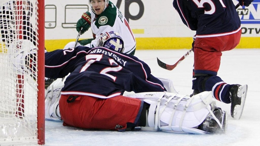 Minnesota Wild's Zach Parise, left, scores against Columbus Blue Jackets' Sergei Bobrovsky (72) of Russia, as Fedor Tyutin, of Russia, defends, during the first period of an NHL hockey game Wednesday, Dec. 31, 2014, in Columbus, Ohio. (AP Photo/Jay LaPrete)