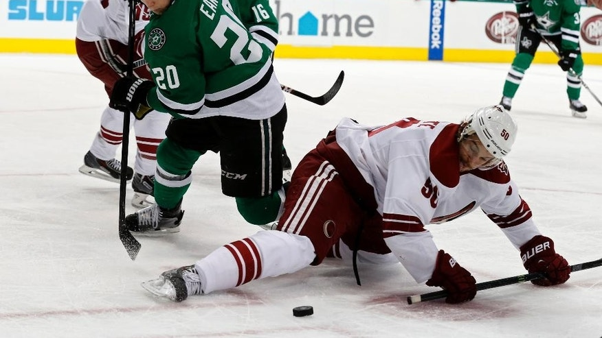 Dallas Stars' center Cody Eakin (20) and Arizona Coyotes' center Antoine Vermette (50) fight for the puck in the first period of an NHL hockey game Wednesday, Dec. 31, 2014, in Dallas. (AP Photo/Sharon Ellman)