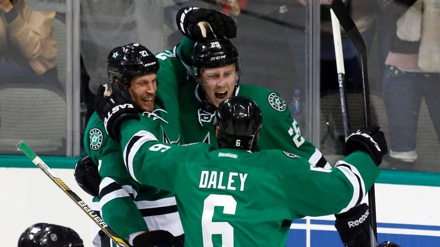 Dallas Stars' right wing Brett Ritchie (25) celebrates with left wig Travis Moen (27) and defenseman Trevor Daley (6) after scoring his first career NHL goal in the second period of an NHL hockey game against the Arizona Coyotes, Wednesday, Dec. 31, 2014, in Dallas. (AP Photo/Sharon Ellman)