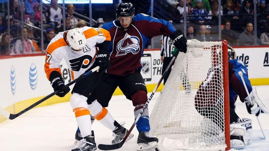 Philadelphia Flyers right wing Wayne Simmonds, left, fights for control of the puck behind the net with Colorado Avalanche defenseman Erik Johnson, center, as goalie Semyon Varlamov, of Russia, covers the crease in the second period of an NHL hockey game Wednesday, Dec. 31, 2014, in Denver. (AP Photo/David Zalubowski)