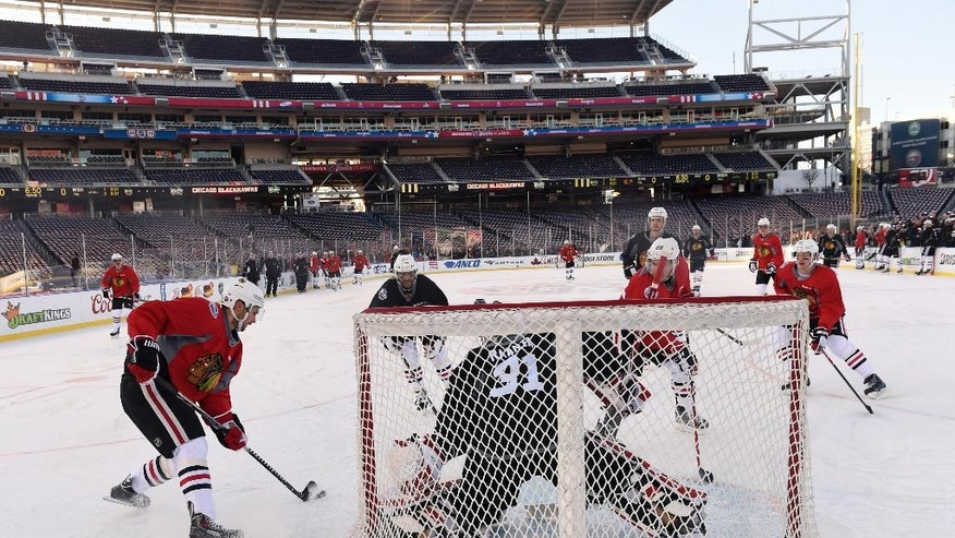 Chicago Blackhawks teammates try to score on goalie Antti Raanta (31), of Finland, at Nationals Park, Wednesday, Dec. 31, 2014, at the beginning of a team practice in preparation for the Winter Classic outdoor NHL hockey game to be held on New Year's Day. The Blackhawks will face off against the Washington Capitals. (AP Photo/Susan Walsh)