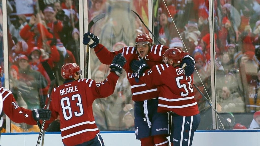 Washington Capitals center Jay Beagle (83) and defenseman Mike Green (52) celebrate with left wing Alex Ovechkin (8), from Russia, after Ovechkin's goal in the first period of the Winter Classic outdoor NHL hockey game against the Chicago Blackhawks at Nationals Park, Thursday, Jan. 1, 2015, in Washington. (AP Photo/Alex Brandon)