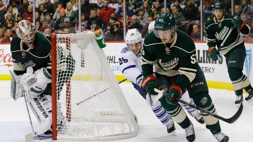 Minnesota Wild center Tyler Graovac (53) controls the puck in front of Toronto Maple Leafs center Mike Santorelli (25) as Wild goalie Darcy Kuemper, left, covers the net during the second period of an NHL hockey game in St. Paul, Minn., Friday, Jan. 2, 2015. (AP Photo/Ann Heisenfelt)