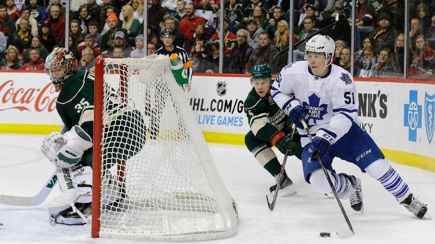 Toronto Maple Leafs defenseman Jake Gardiner (51) brings the puck around the net in front of Minnesota Wild defenseman Christian Folin (5), of Sweden, as Wild goalie Darcy Kuemper, left, covers the net during the second period of an NHL hockey game in St. Paul, Minn., Friday, Jan. 2, 2015. (AP Photo/Ann Heisenfelt)