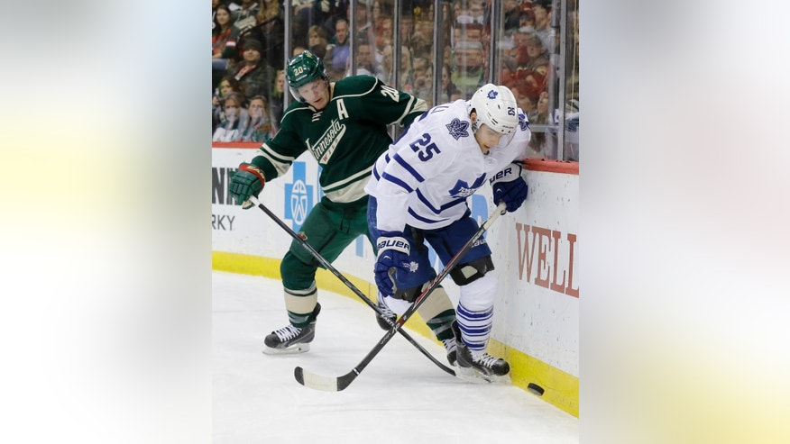 Toronto Maple Leafs center Mike Santorelli (25) and Minnesota Wild defenseman Ryan Suter (20) chase the puck during the second period of an NHL hockey game in St. Paul, Minn., Friday, Jan. 2, 2015. (AP Photo/Ann Heisenfelt)