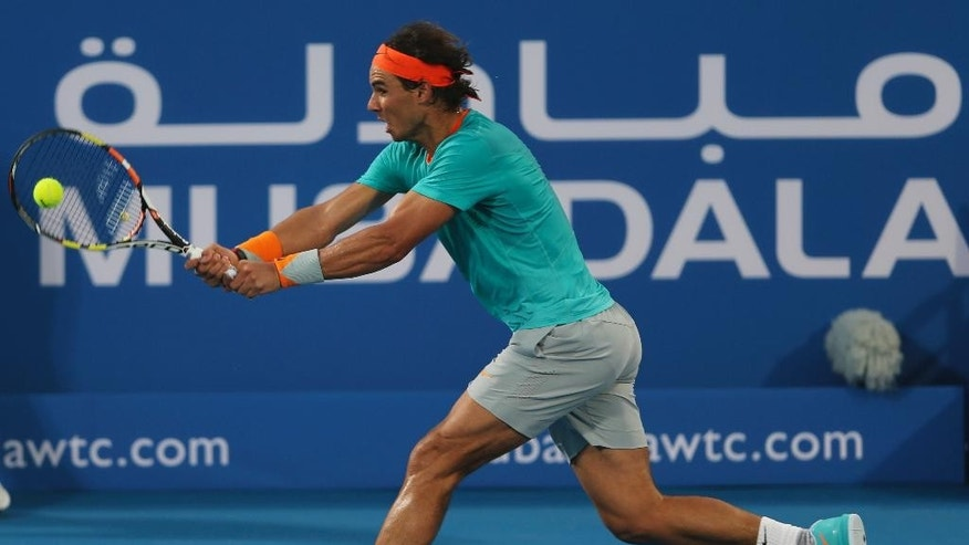 Spain's Rafael Nadal returns the ball against Britain's Andy Murray on the second day of the Mubadala World Tennis Championship in Abu Dhabi, United Arab Emirates, Friday, Jan. 2, 2015. (AP Photo/Kamran Jebreili)