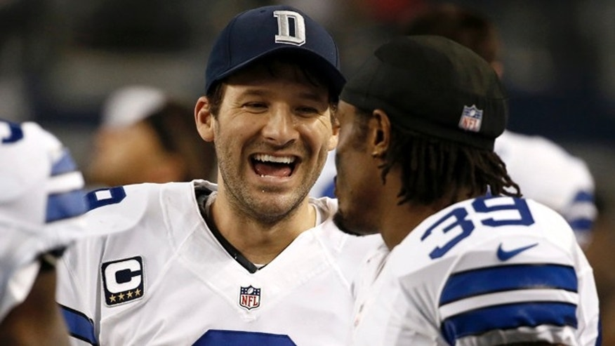 Dallas Cowboys quarterback Tony Romo, left, laughs as he talks with teammate Brandon Carr (39) on the sideline during the second half of an NFL football game against the Indianapolis Colts, Sunday, Dec. 21, 2014, in Arlington, Texas. (AP Photo/Brandon Wade)