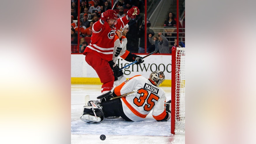 Carolina Hurricanes' Eric Staal (12) celebrates his goal next to Philadelphia Flyers goalie Steve Mason (35) during the second period of an NHL hockey game in Raleigh, N.C., Friday, Jan. 2, 2015. (AP Photo/Karl B DeBlaker)
