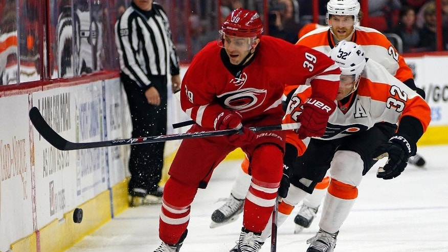 Carolina Hurricanes' Patrick Dwyer (39) chips the puck ahead of Philadelphia Flyers' Mark Streit (32) during the second period of an NHL hockey game in Raleigh, N.C., Friday, Jan. 2, 2015. (AP Photo/Karl B DeBlaker)