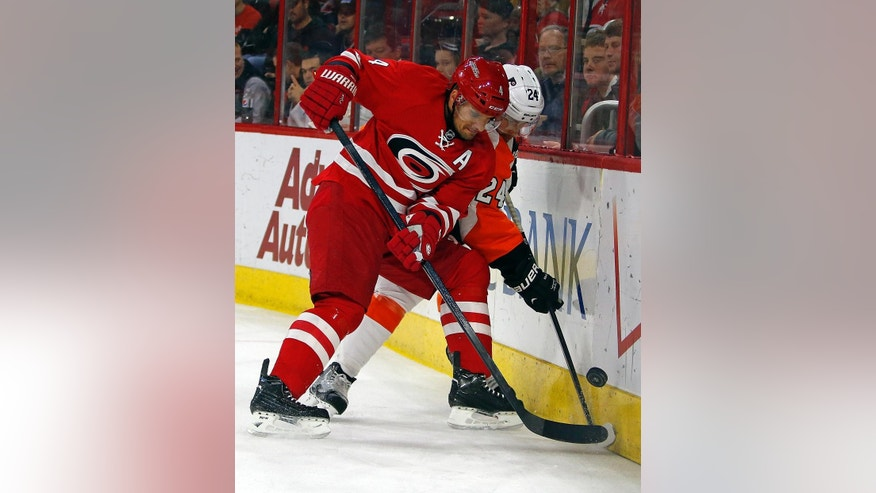 Carolina Hurricanes' Andrej Sekera (4), of Slovakia, battles along the boards with Philadelphia Flyers' Matt Read (24) during the first period of an NHL hockey game in Raleigh, N.C., Friday, Jan. 2, 2015. (AP Photo/Karl B DeBlaker)