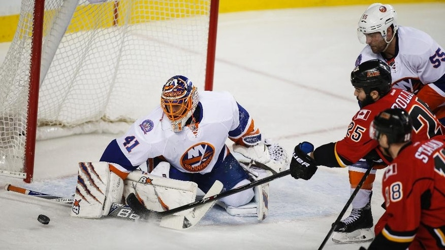 New York Islanders goalie Jaroslav Halak, left, from Slovakia, blocks the net as Calgary Flames' Brandon Bollig chases the puck during first-period NHL hockey gme action in Calgary, Alberta, Friday, Jan. 2, 2015. (AP Photo/The Canadian Press, Jeff McIntosh)