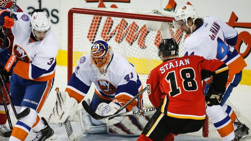New York Islanders goalie Jaroslav Halak, centre, from Slovakia, pounces on the puck as Calgary Flames' Matt Stajan looks for a rebound during second-period NHL hockey gme action in Calgary, Alberta, Friday, Jan. 2, 2015. (AP Photo/The Canadian Press, Jeff McIntosh)