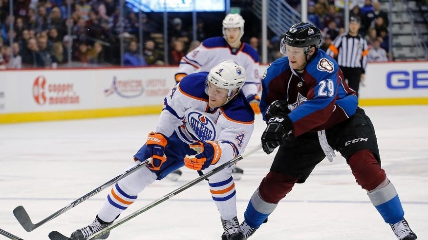 Colorado Avalanche center Nathan MacKinnon (29) and Edmonton Oilers left wing Taylor Hall (4) chase the puck during the first period of an NHL hockey game Friday, Jan. 2, 2015, in Denver. (AP Photo/Jack Dempsey)