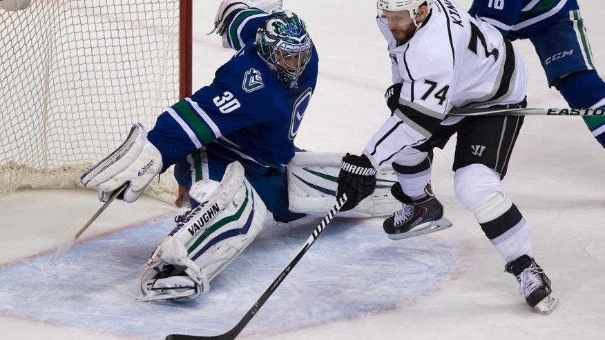 Los Angeles Kings' Dwight King, right, shoots on Vancouver Canucks goalie Ryan Miller during the second period of an NHL hockey game Thursday, Jan. 1, 2015, in Vancouver, British Columbia. (AP Photo/The Canadian Press, Darryl Dyck)