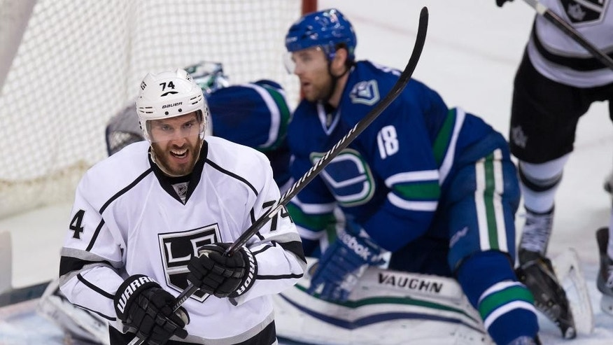 Los Angeles Kings' Dwight King (74) celebrates after scoring a goal, in front of Vancouver Canucks' Ryan Stanton, back right, and goalie Ryan Miller during the second period of an NHL hockey game Thursday, Jan. 1, 2015, in Vancouver, British Columbia. (AP Photo/The Canadian Press, Darryl Dyck)