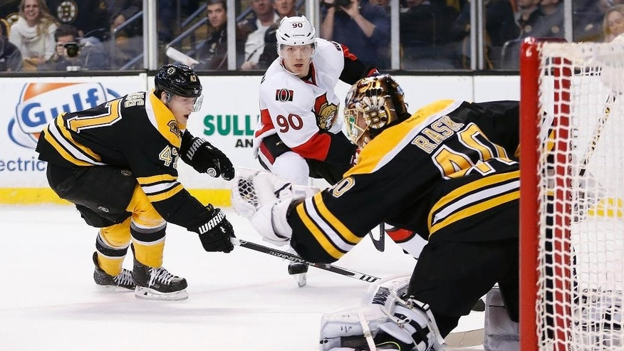 Boston Bruins' Tuukka Rask (40), of Finland, catches the shot by Ottawa Senators' Alex Chiasson (90) as the Bruins' Torey Krug (47) defends during the first period of an NHL hockey game in Boston, Saturday, Jan. 3, 2015. (AP Photo/Michael Dwyer)
