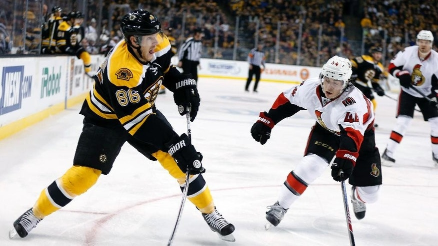 Boston Bruins' Kevan Miller (86) takes a shot as Ottawa Senators' Jean-Gabriel Pageau (44) defends during the second period of an NHL hockey game in Boston, Saturday, Jan. 3, 2015. (AP Photo/Michael Dwyer)