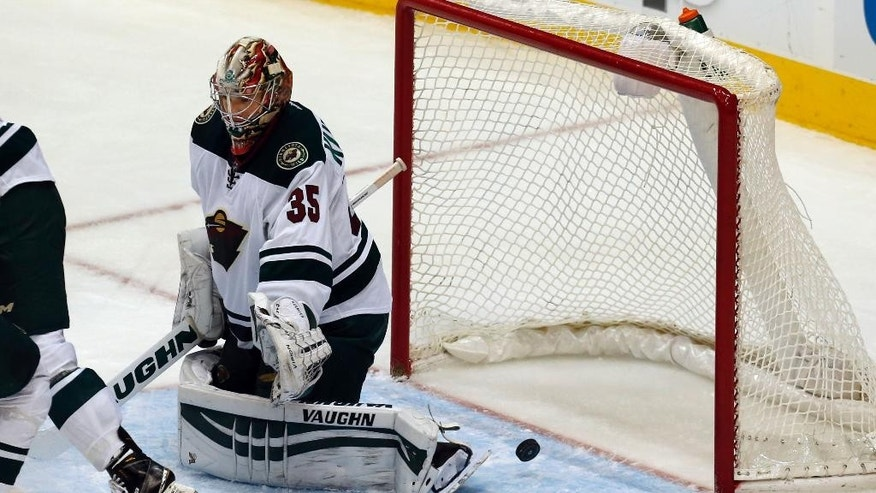 A puck scoots by Minnesota Wild goalie Darcy Kuemper (35) for a Dallas Stars goal during the second period of an NHL hockey game Saturday, Jan. 3, 2015, in Dallas. (AP Photo/John F. Rhodes)