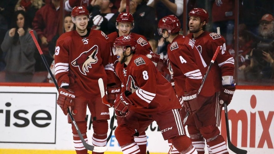 Arizona Coyotes' Tobias Rieder (8), of Germany, is surrounded by teammates Oliver Ekman-Larsson (23), of Sweden, Zbynek Michalek (4), of the Czech Republic, Kyle Chipchura (24) and Lauri Korpikoski after Rieder's goal against the Columbus Blue Jackets during the first period of an NHL hockey game Saturday, Jan. 3, 2015, in Glendale, Ariz. (AP Photo/Ross D. Franklin)
