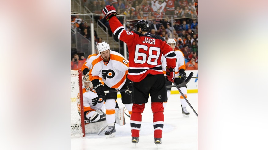 New Jersey Devils right wing Jaromir Jagr (68), of the Czech Republic, celebrates after scoring his third goal of the game against the Philadelphia Flyers during the second period of an NHL hockey game, Saturday, Jan. 3, 2015, in Newark, N.J. (AP Photo/Julio Cortez)