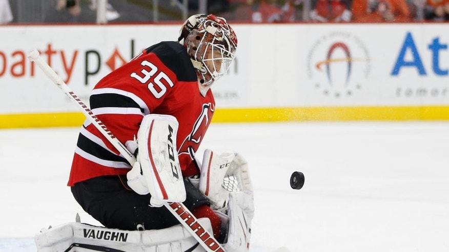 New Jersey Devils goalie Cory Schneider makes a save against the Philadelphia Flyers during the first period of an NHL hockey game, Saturday, Jan. 3, 2015, in Newark, N.J. (AP Photo/Julio Cortez)