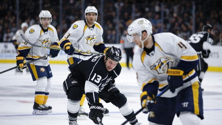 Los Angeles Kings' Kyle Clifford, center, pressures Nashville Predators' Ryan Ellis, foreground during the second period of an NHL hockey game Saturday, Jan. 3, 2015, in Los Angeles. (AP Photo/Jae C. Hong)