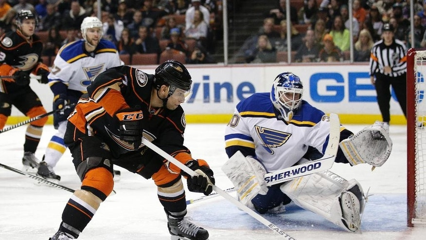 Anaheim Ducks' Andrew Cogliano, left, moves the puck as St. Louis Blues goalie Martin Brodeur watches during the second period of an NHL hockey game Friday, Jan. 2, 2015, in Anaheim, Calif. (AP Photo/Jae C. Hong)