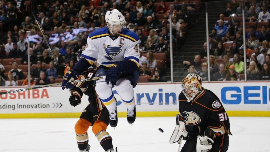 St. Louis Blues' David Backes, center, jumps out of the way of the puck in front of Anaheim Ducks goalie Frederik Andersen, of Denmark, during the first period of an NHL hockey game Friday, Jan. 2, 2015, in Anaheim, Calif. (AP Photo/Jae C. Hong)