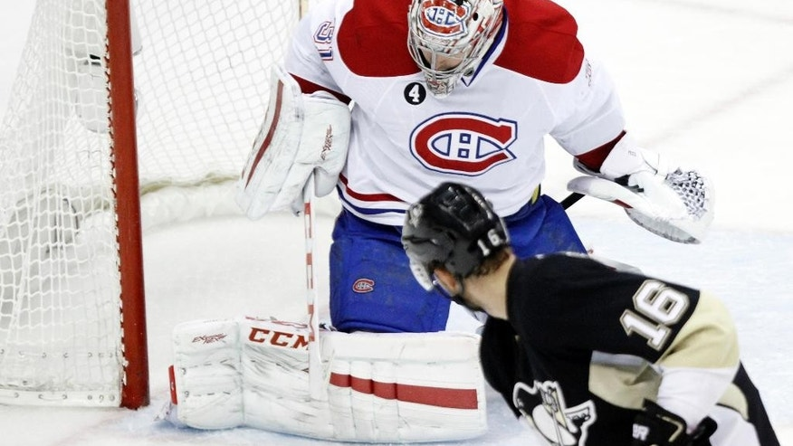 Montreal Canadiens goalie Carey Price (31) stops a shot by Pittsburgh Penguins' Brandon Sutter (16) during the second period of an NHL hockey game in Pittsburgh, Saturday, Jan. 3, 2015. (AP Photo/Tom E. Puskar)