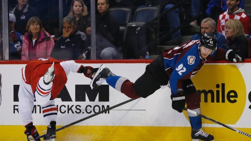 Columbus Blue Jackets defenseman David Sevard, left, tumbles into the boards after missing a check on Colorado Avalanche left wing Gabriel Landeskog, of Sweden, in the second period of an NHL hockey game Sunday, Jan. 4, 2015, in Denver. (AP Photo/David Zalubowski)