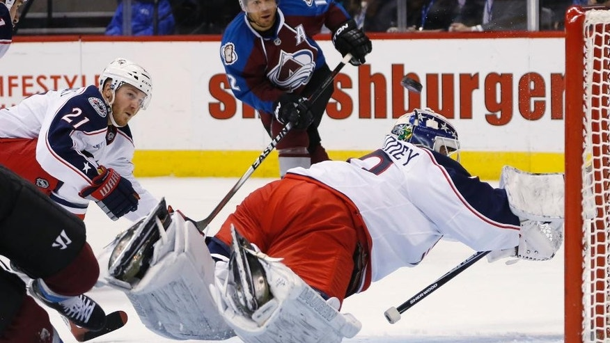 Columbus Blue Jackets goalie Curtis McElhinney, right, dives to stop a shot off the stick of Colorado Avalanche right wing Jarome Iginla, back, as Blue Jackets defenseman James Wisniewski, (21), covers in the second period of an NHL hockey game Sunday, Jan. 4, 2015, in Denver. (AP Photo/David Zalubowski)
