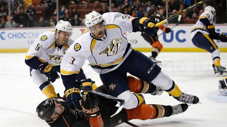 Anaheim Ducks' Corey Perry, bottom, and Nashville Predators' Seth Jones fall to the ice as they compete for the puck during the second period of an NHL hockey game Sunday, Jan. 4, 2015, in Anaheim, Calif. (AP Photo/Jae C. Hong)